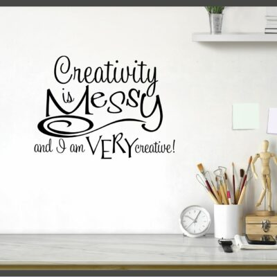 """""""Creativity is messy and I am very creative"""" written in black vinyl lettering on multiple lines with mixed font sizing applied to a white wall to the left of a small clock and ceramic cup holding paintbrushes"""
