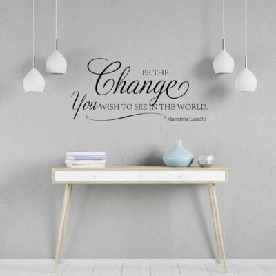 """""""Be the Change You wish to see in the world. -Mahatma Gandhi"""" written on multiple lines and mixed fonts in black vinyl lettering on a light grey wall between 4 hanging lamps over a console table which contains stacked books and a small vase"""