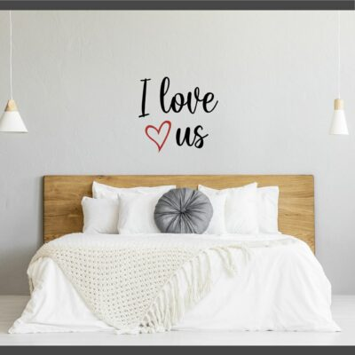 """""""I love us"""" written on two lines in black vinyl lettering with a red heart on the second line to the left of """"us"""" applied to a light grey wall over a light brown, king-sized headboard"""