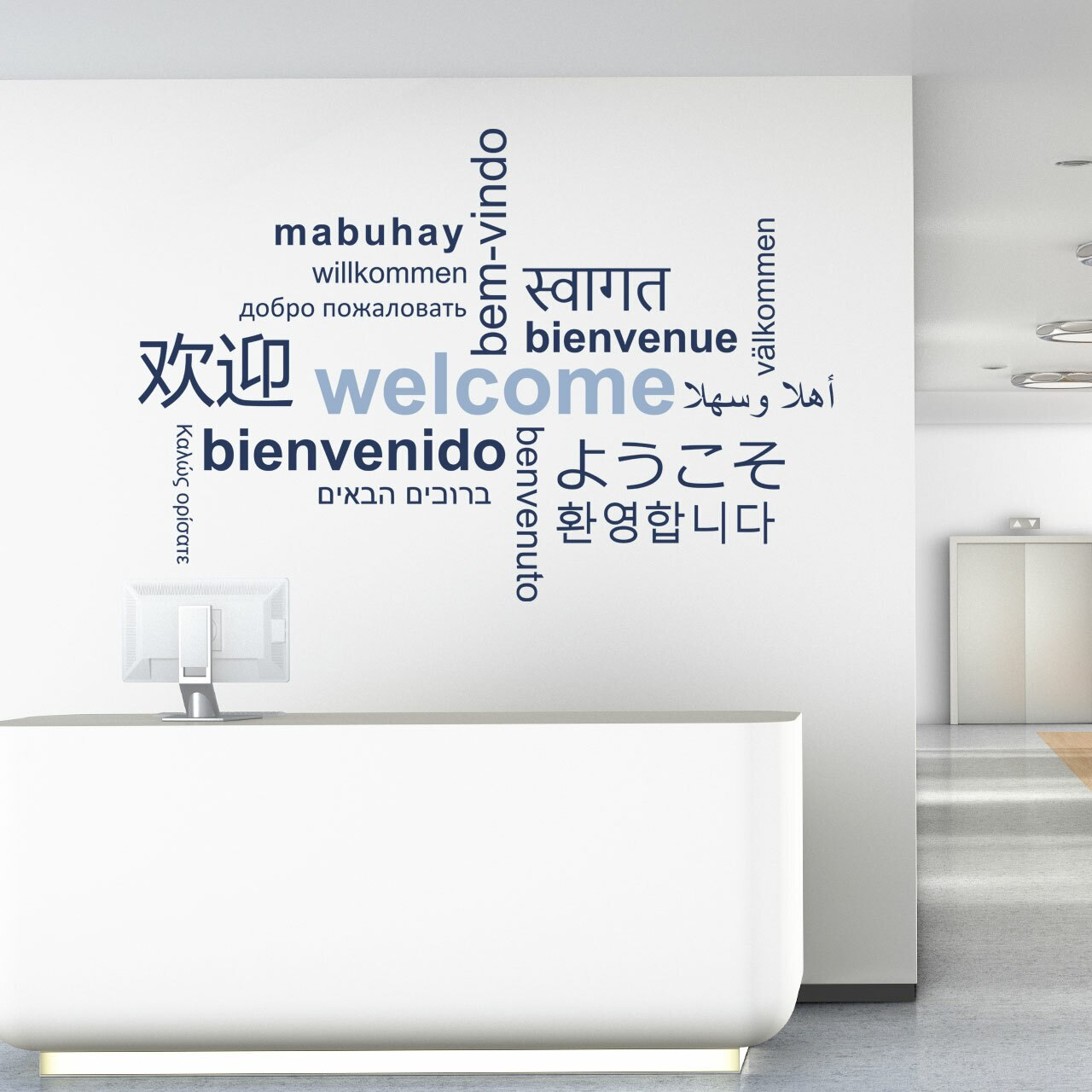 Welcome word cloud in multiple languages, navy blue and sky colored vinyl lettering on white wall in the reception area of a business